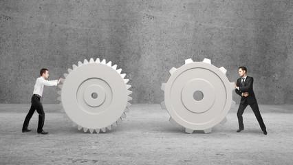 two businessman pushing gears