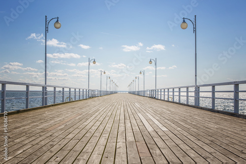 Fotobehang Brug Old empty wooden pier over the sea shore with copy space