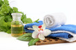 Fresh spa elements with massage oil, towels, orchid greens