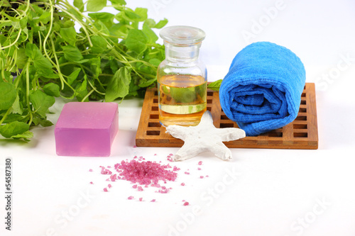 Spa background with soap, oil, bath salts, towel, green leafs