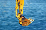 Rusty yellow bulldozer scoop over sea water