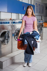 Upset Woman Holding Basket Full Of Dirty Clothes