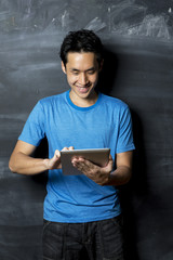 Chinese man using tablet PC next to blackboard.