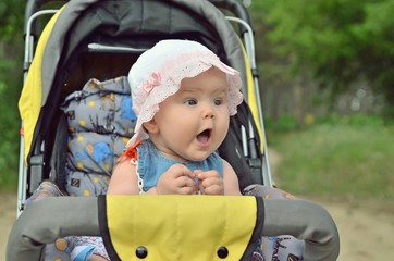 Surprised baby in a stroller