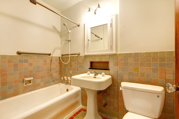 Bathroom with old antique fixtures and white tub.