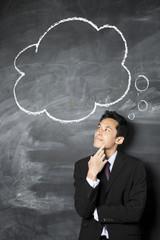 Chinese businessman looking at speech bubble on blackboard.