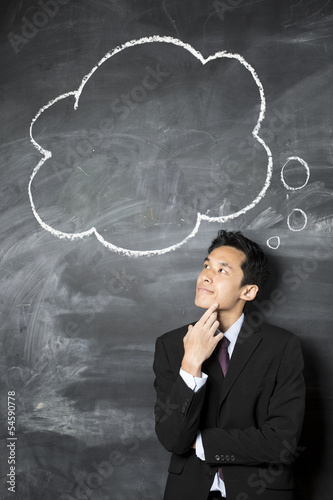 Chinese businessman looking at speech bubble on blackboard.