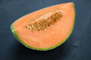 Segment of ripe cantaloupe melon on black wooden boards