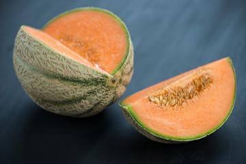 Ripe cantaloupe melon on black wooden boards