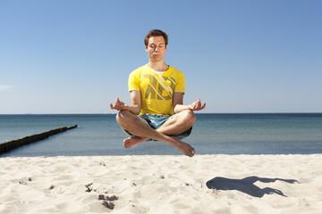 junger Mann meditiert schwebend am Strand