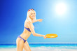 Smiling female in bikini playing with frisbee on a beach