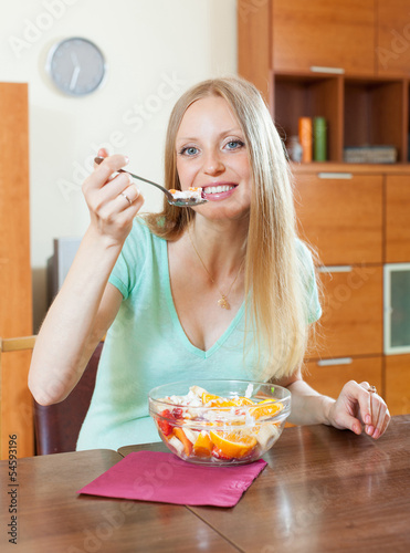 blonde woman eating  fruit salad at home