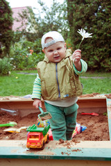 builder boy playing in a sandbox