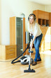 Happy long-haired woman in headphones cleaning with vacuum clean