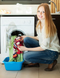blonde woman putting clothes in to  machine
