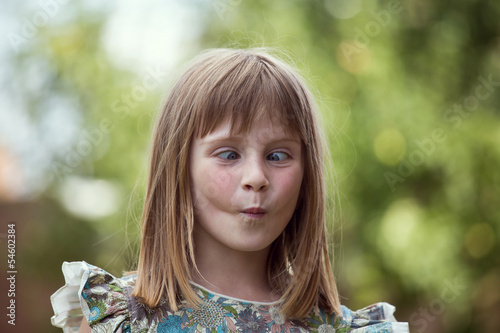 Portrait cross-eyed young girl on the nature in summer day