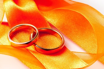 gold wedding rings on orange ribbon