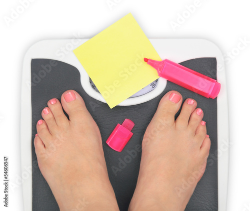 Woman' s feet on bathroom scale and blank notepaper