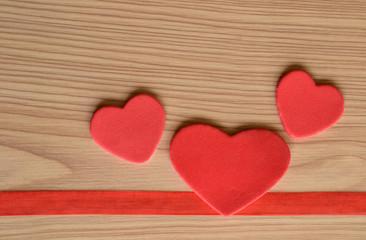 Tres corazones sobre fondo rústico de madera
