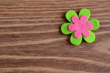 Flor rosa y verde sobre fondo rústico de madera