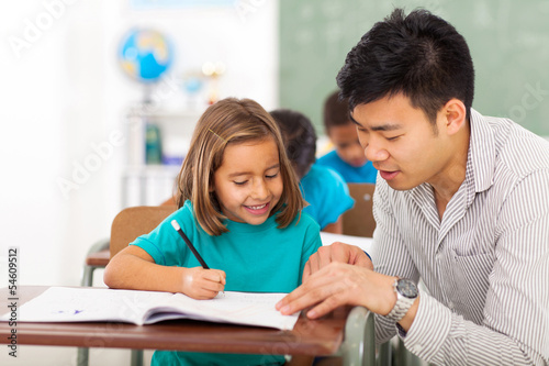 preschool teacher helping little girl with class work