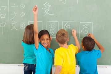 schoolgirl after writing chinese on blackboard