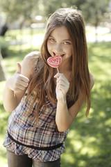 Happy girl eating lollipop