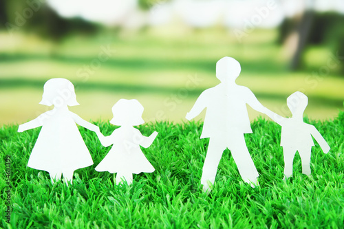 Paper people on green grass on bright background