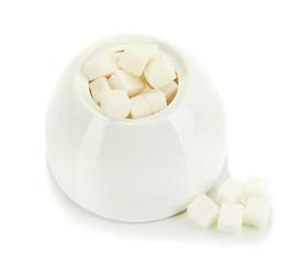 Refined sugar in white sugar bowl on grey background
