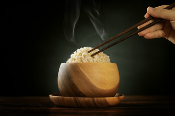 Cooked organic basmati brown rice with steam and chopsticks