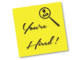 You're hired. Employment concept on yellow sticker note.