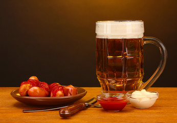 Beer and grilled sausages on wooden table on brown background