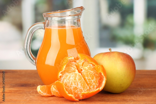 Full jug of multivitamin juice on bright background