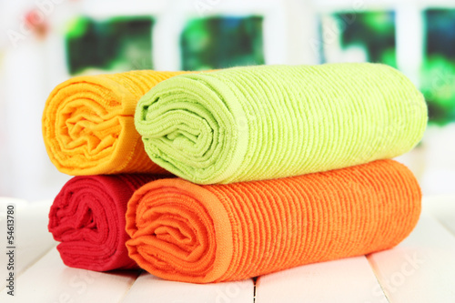 Colorful towels on wooden table on window background