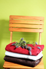 Towels and flowers on wooden chair on green background