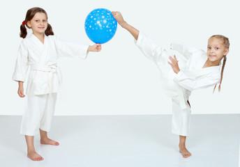 Two little girls with blue ball beat a karate kick leg