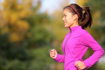 Asian woman running in autumn forest in fall