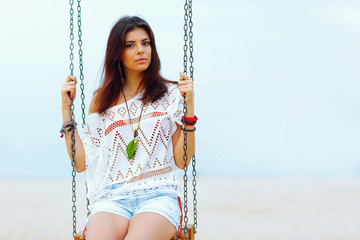Young beautiful woman sitting on a swing on the beach