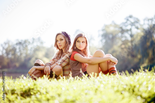 two girls sitting back to back