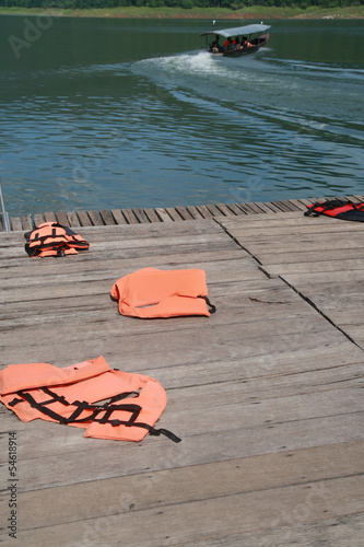 life vest on wood floor with a boat on river background