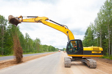 Excavator working on the construction of the road