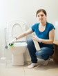 Smiling housewife cleaning toilet with sponge