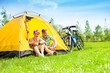 Yong couple with bikes in a tent