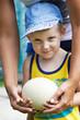 Little boy holding an ostrich eggj