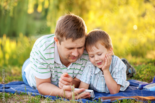 Father and son with a smartphone outdoors