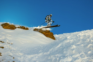 Skier jumps from a cliff during fast motion