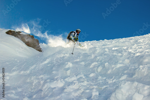 Skier in deep snow around the rock