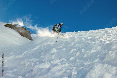 Skier in deep snow around the rock