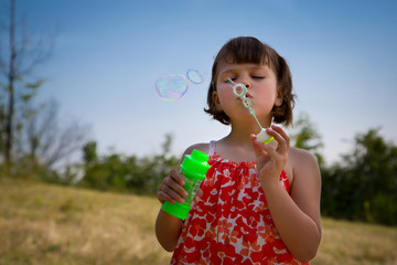 lovely little girl blowing soap bubbles. portrait outdoor.