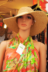 Woman mannequin dressed in a colourful summer dress and a straw